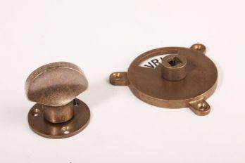 Toiletslot brons antiek gemaakt van messing. Deze wc sluiting heeft aan de binnenzijde een platte knop en aan de buitenzijde is Vrij/Bezet te zien.